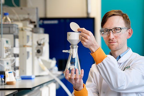 Lech Milroy, UD Chemical Biology, Dept of Biomedical Engineering, TU Eindhoven, demonstrating the simple filtration principle for simple scaled-up production of pure Z-endoxifen. In the background a labour-intensive high pressure setup to produce the same in low quantities.