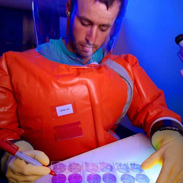 CDC scientist Zach Braden counts viral plaques within fixed monolayers of cells over a light box in order to titrate a viral stock in BSL-4 Lab. Image courtesy James Gathany, CDC.