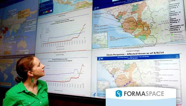 Centers for Disease Control and Prevention (CDC) communications specialist, Molly, standing in front of a display of maps and graphs outlining current epidemiologic trends in the 2014 West African Ebola outbreak. Image courtesy Daniel DeNoon, CDC